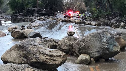 Santa Barbara County Firefighters work admist flood waters and debris flow during heavy rains in Montecito on Tuesday. (AAP)