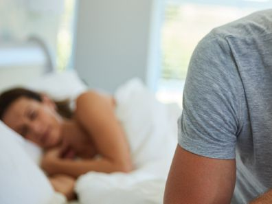 Man sitting on bed with woman lying down behind him.