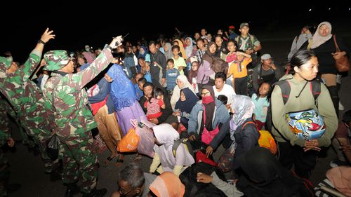 Thousands of desperate Indonesian earthquake and tsunami survivors have converged on Palu's airport in a bid to leave the devastated city