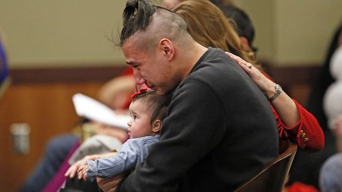 Savanna LaFontaine-Greywind's boyfriend Ashston Matheny holds their daughter, Haisley Jo, as victim impact statements are read during the sentencing of Brooke Crews.