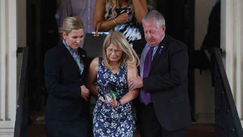 Faye Leveson is comforted by her husband Mark and a funeral director. (AAP)
