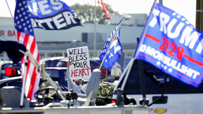 Joe Biden supporter Bill Morris from Middleburg directs his sign at the driver of a truck hauling a boat decorated with flags supporting President Donald Trump along Blanding Blvd. in Orange Park, Florida on Election Day Tuesday November 3, 2020. [Bob Self/Florida Times-Union via AP]