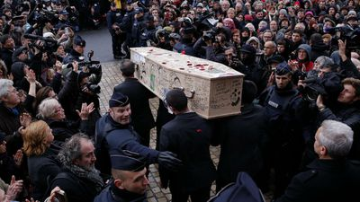 Police attempt to clear a path as the coffin of Bernard Verlhac, aka Tignous, leaves City Hall. Thousands turned out for the funeral services. (AP)