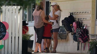 Parents talk to each other as they drop children off to school. (AAP)