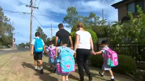 The three girls make their way to school with their parents. (9NEWS)