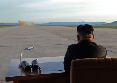 An undated photo from the North Korean Central News Agency (KCNA) showing the country's leader Kim Jong Un (R), guiding a launching of the medium-to-long range ballistic rocket Hwasong-12 at an unspecified location. (AAP)