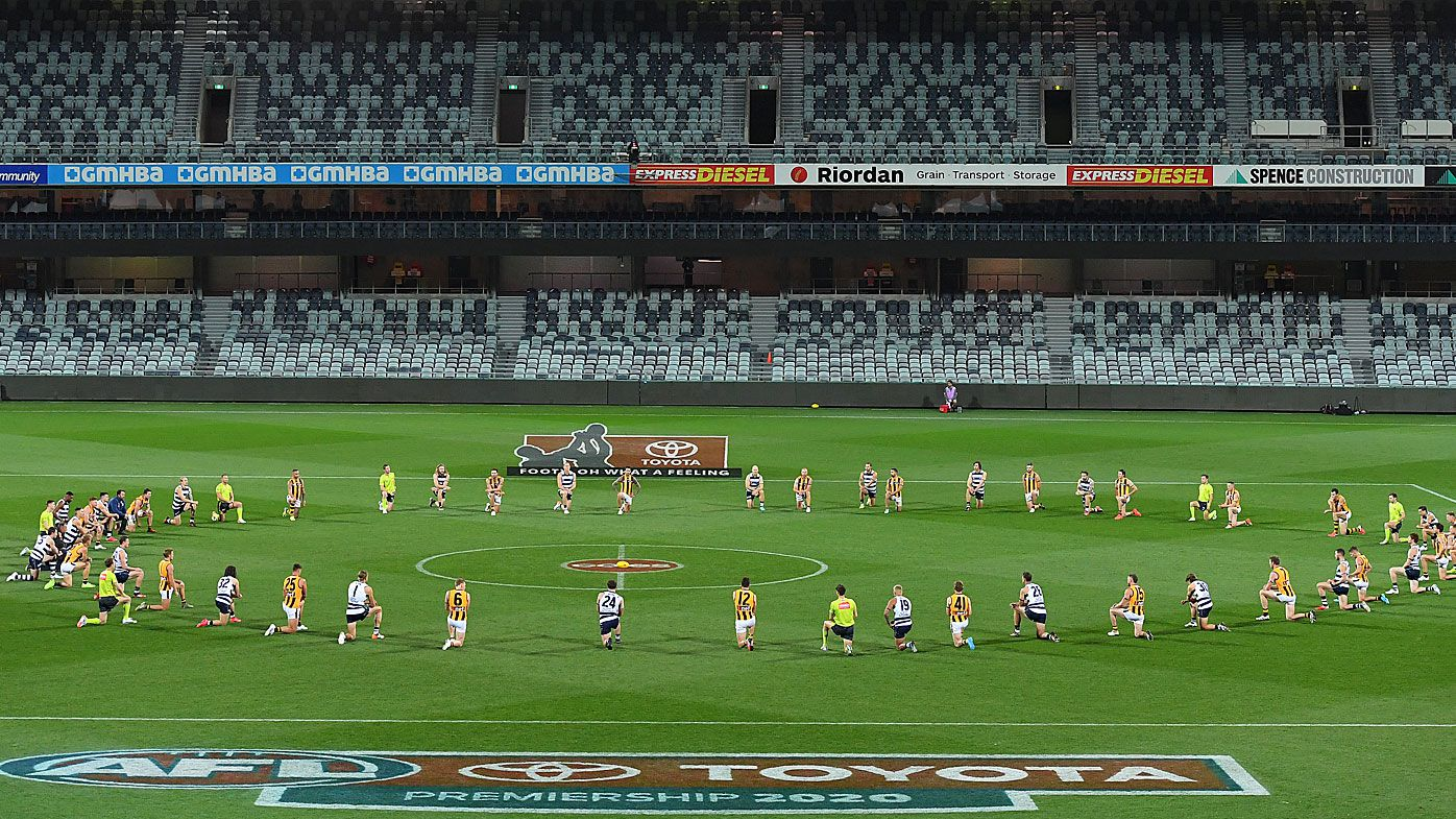 Players take take a knee in support of the Black Lives Matter movement before the round 2 AFL match