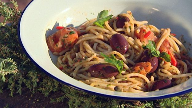 Spaghetti tossed in a wok with olives, anchovies and capers