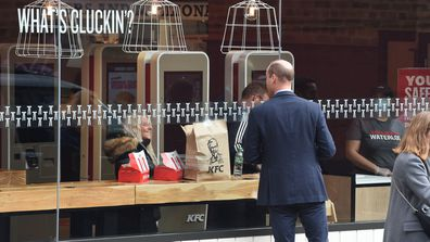 Prince William, Duke of Cambridge speaks to a member of the public through the window of a KFC restaurant before attending the launch of the Hold Still campaign at Waterloo Station on October 20, 2020 in London, England.