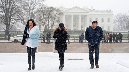 Snow begins to fall at President's Park across the street from the White House, in Washington, DC. (AAP)
