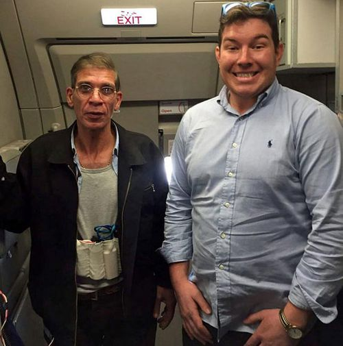 English passenger Ben Innes posing for a photo with the hijacker, who can be seen wearing a fake suicide belt.
