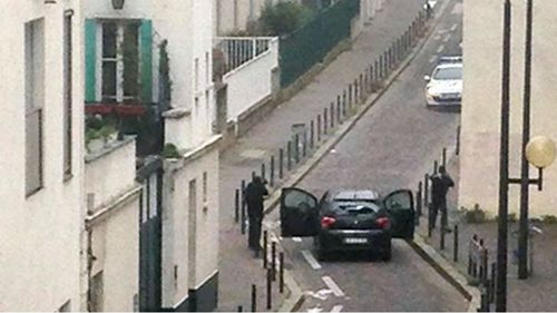 The gunmen face police officers near the offices of the Paris offices of satirical newspaper Charlie Hebdo. (Getty)