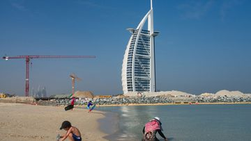 Families play on a public beach with the Burj al-Arab hotel behind them in Dubai, United Arab Emirates, Friday, May 29, 2020