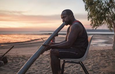 Local Aboriginal man play didgeridoo on the beach. Journey into East Arnhem Land, Northern Territory