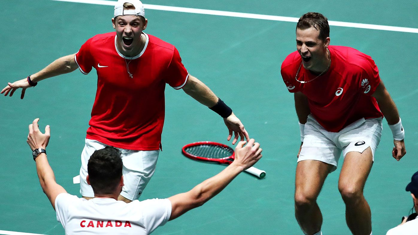 Vasek Pospisil and Denis Shapovalov celebrate with Canada team captain Frank Dancevic after winning