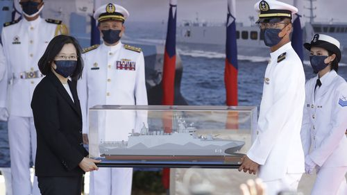 Taiwan's President Tsai Ing-wen, left, holds a model ship during the commissioning ceremony of the the domestically made Ta Jiang warship.