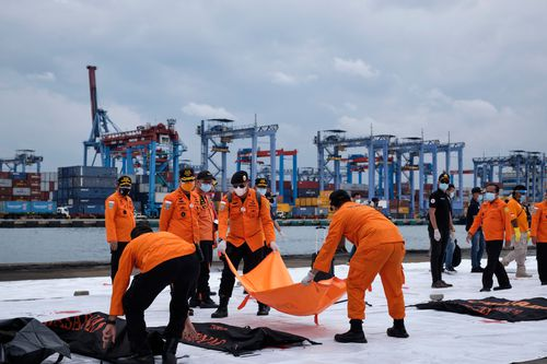 Indonesian search and rescue personnel carry body bags with human remains and debris from Sriwijaya Air flight SJ182 to be examined by investigators