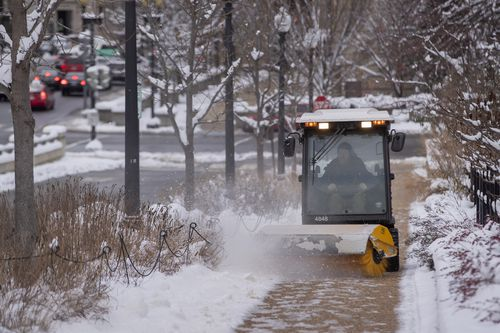 A worker clears a sidewalk of snow and ice after a weekend winter storm in Washington.