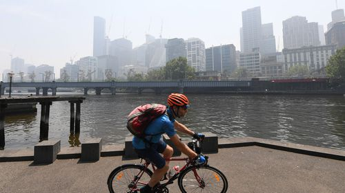 A cyclist rides along the Yarra River in Melbourne, Friday, January 3, 2020. A smoke haze has drifted over the city from the bushfires in East Gippsland