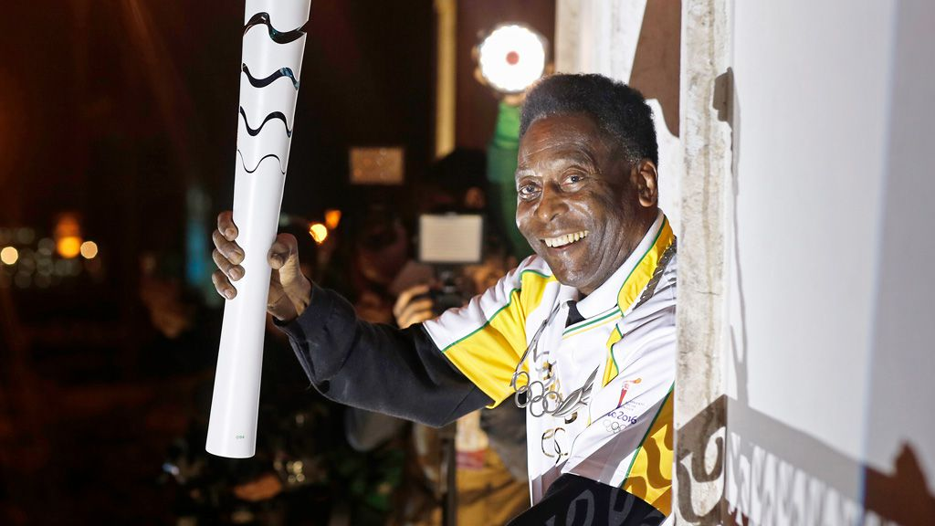 Former football player Pele holding the Olympic flame at the Pele Museum in Santos, Sao Paulo State, on July 22, 2016. (AFP)
