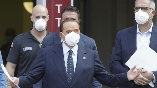 Italian former Premier Silvio Berlusconi is flanked by his personal physician Alberto Zangrillo, right, as he leaves the San Raffaele hospital in Milan, Italy, Monday, Sept. 14, 2020