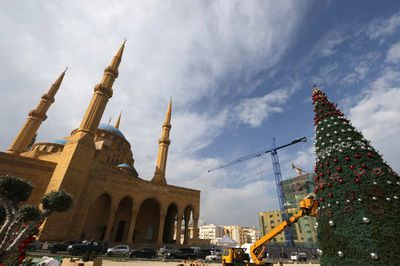 Workers decorate a Christmas tree next to the Mohammed Al-Amin mosque in downtown Beirut. (Joseph Eid/AFP/Getty)