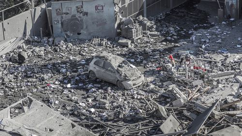 A destroyed car among the rubble of a building damaged after an Israeli airstrike in Gaza.
