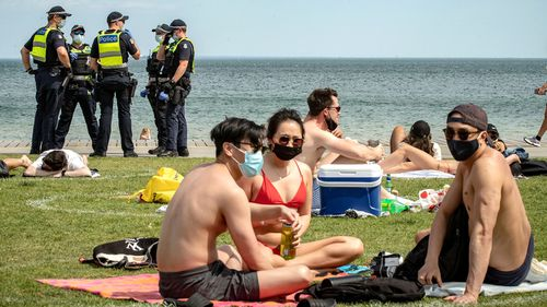 Victoria Police patrol St Kilda beach in Melbourne, as groups of young people wear masks in the sunshine.