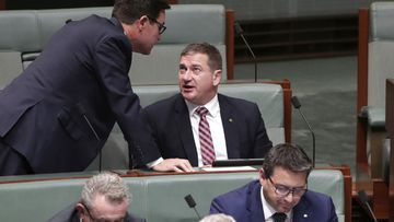Minister David Littleproud approaches the backbench for a discussion with Nationals MP Llew O'Brien during Question Time at Parliament House, in 2019.