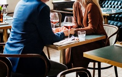 A couple holding hands while sitting down at a table and drinking red wine in a restaurant for lunch together.