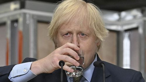 Britain's Prime Minister Boris Johnson sips water as he delivers a speech during a visit to Dudley College of Technology in Dudley, England, Tuesday June 30, 2020.