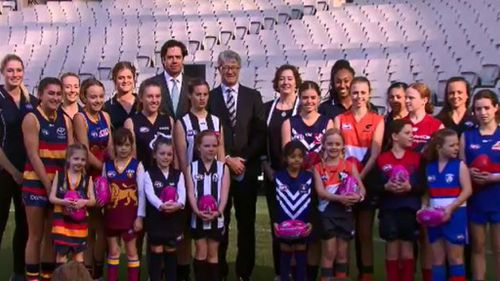 AFL CEO Gillon McLachlan and Chairman Mike Fitzpatrick with girls football players from the eight teams. (9NEWS)