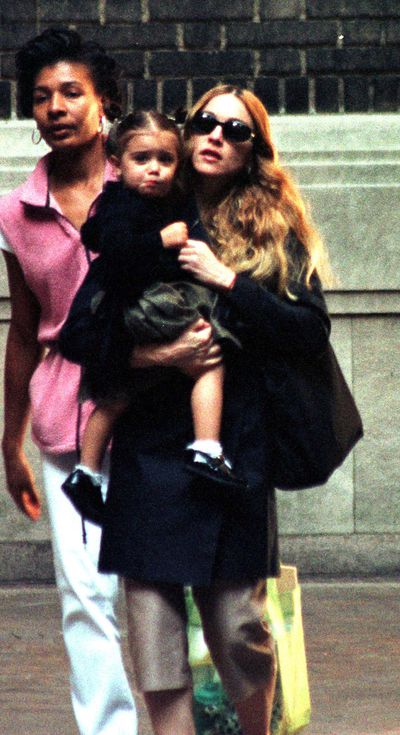 Then: Madonna and baby daughter Lourdes with her nanny in 1998.