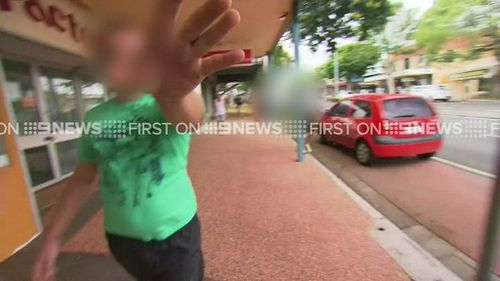 The son of the accused woman scuffles with the media outside court. (9NEWS)