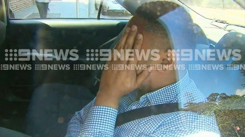 The man accused of staring into a family home in Collaroy is escorted to Manly Police Station.