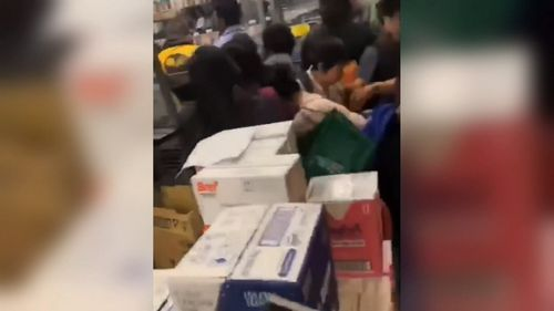 Shoppers scramble over each other to get to the tins of baby formula.