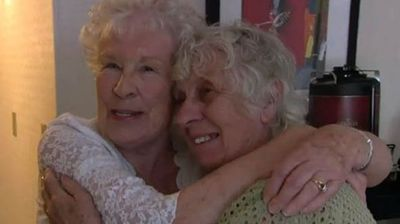 Twins Ann Hunt (in green) and Elizabeth Hamel hug as they are reunited for the first time. (Supplied)