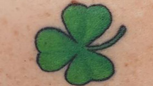 The woman has a clover tattoo on her shoulder.