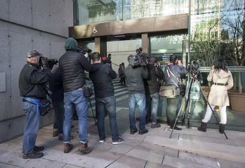 Members of the media photograph a line of people waiting to enter a courtroom to attend a bail hearing for Meng Wanzhou.