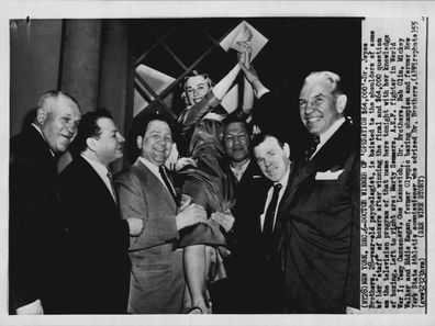 """Doctor Winner of 'Operation $64,000' - Dr Joyce Brothers, 28-year-old psychologist, is hoisted to the shoulders of some of her """"staff"""" of boxers after winning the final and $64,000 question on the the television program of that name."""