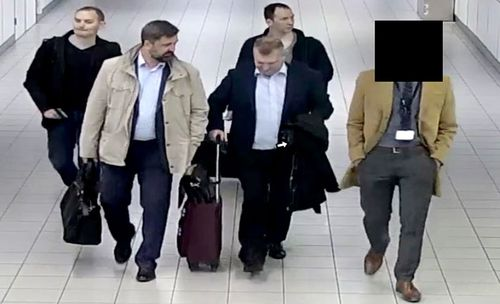 An image released and manipulated by the Dutch Defense Ministry shows four Russian officers of the GRU escorted to their flight after being expelled from the Netherlands on April 13, 2018.