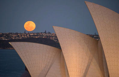 A super moon rises above the skyline behind the Sydney Opera House on September 28, 2015.