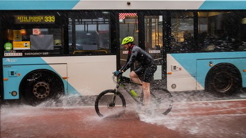 A cyclist is sprayed with water by a bus in Paddington, Sydney.