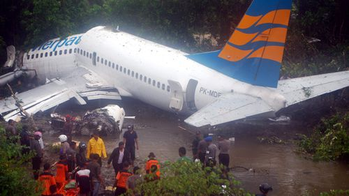 Rescuers try to find survivors from a commercial plane after it skidded off the runway at Manokwari airport in West Papua, Indonesia on April 2010. An Indonesian plane with over 100 people on board skidded off the runway injuring at least 20 people.