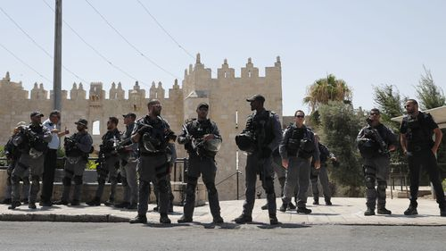 Heavily armed officers guard the sacred site following the shooting.