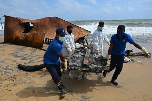 Members of Sri Lankan Navy remove debris washed ashore from the Singapore-registered container ship MV X-Press Pearl.