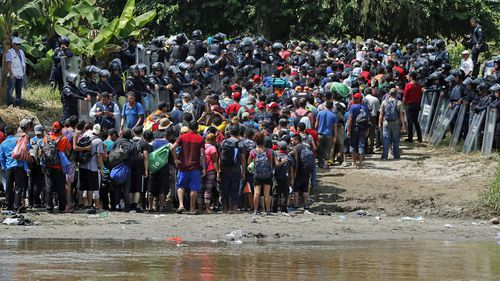 Mexican Riot police allow hundreds of members of the second migrant caravan, mostly Hondurans, cross the Suchiate river, from Guatemala, in Tecun Uman, Guatemala.