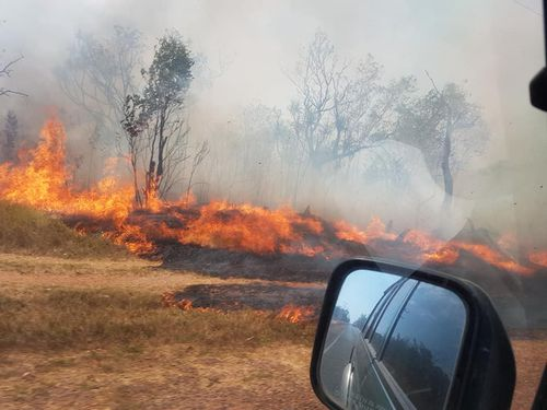 Fire crews are rushing to extinguish a large bushfire that is burning in a rural area near Darwin.