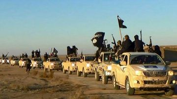 Photo of Islamic state soldiers with guns, flags, vehicles