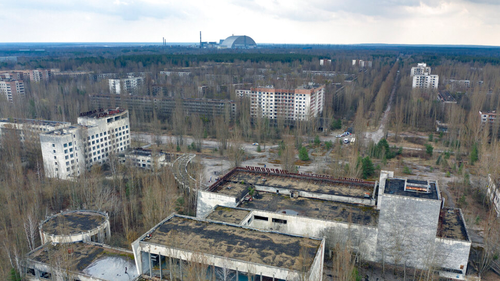 A view of the ghost town of Pripyat with a shelter covering the exploded reactor at the Chernobyl nuclear plant in the background.